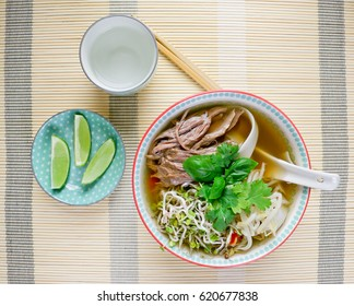 Vietnamese soup Pho Bo with lime, chinese sticks and water, horizontal