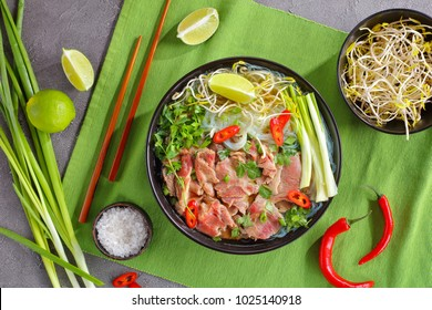Vietnamese soup Pho Bo with rice noodle, raw sirloin beef slices, bean sprouts, lime, spring onion in black bowl with chopsticks, hot peppers on green table mat, view from above, close-up