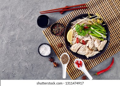 vietnamese soup Pho Ga with chicken breast, rice noodles, bean sprouts, spices and fresh herbs in a black bowl on a bamboo mat on a concrete table, horizontal view from above, copy space, flatlay