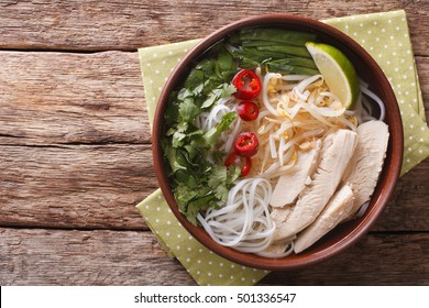 Vietnamese soup Pho Ga with chicken and rice noodles, bean sprouts and chilli in a bowl close-up. Horizontal view from above