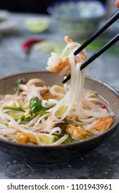 Vietnamese soup pho with seafood in a plate on a gray background