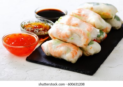 Vietnamese spring rolls - rice paper, lettuce, salad, vermicelli, noodles, shrimps, fish sauce, sweet chili, soy, lemon, veletables. Copy space. Asian and thai food. Traditional national cuisine