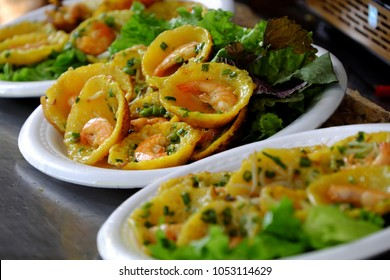 Vietnamese street food, yellow and delicious pancakes on plate at cuisine fair at Ho Chi Minh city, Vietnam, cakes make from rice flour, fresh shrimp, beansprouts, scallion in circle shape