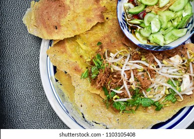 Vietnamese stuffed crispy omelette, top view with sliced cucumber and onion in vinegar, local authentic style, healthy Asian food concept