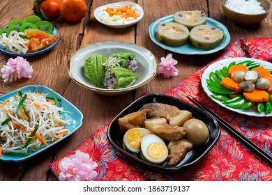Nourriture vietnamienne pour le Tet, nourriture traditionnelle pour la nouvelle année lunaire : ventre de porc aux oeufs durs braisés à l'eau de coco, cornichons mixtes, riz et autres aliments Tet sur fond