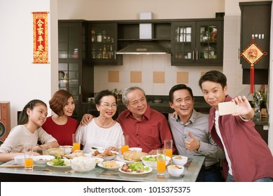 Vietnamese teenage boy taking selfie with his family at Tet celebration dinner. Scrolls wishing luck and wealth in the background