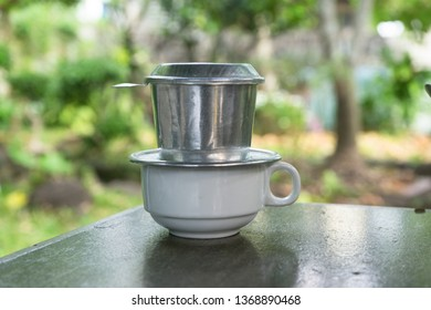 Vietnamese traditional coffee with drip filter (phin). The bean is grind and put in the filter with hot water. It will then drip coffee drops. The below cup will take the drops down within few minutes