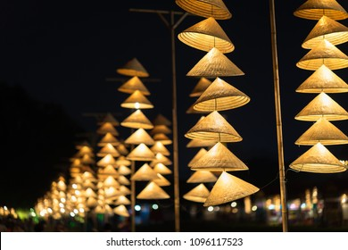 Vietnamese traditional conical hats hanging on wire for decoration.