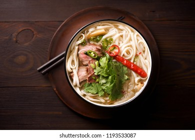 Vietnamese traditional soup Pho Bo with beef and fresh coriander on dark wooden background