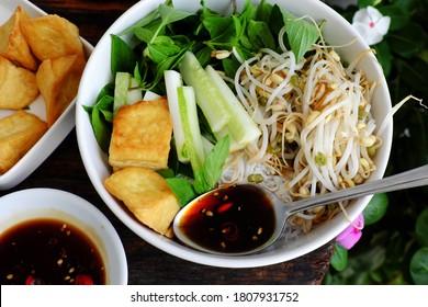 Un repas vietnamien végétalien pour un déjeuner rapide avec des aliments faits maison, des nouilles douces au riz vermicelli et du tofu frit, concombre, germes de haricots, sauce de soja, délicieux plat végétarien sur fond bois