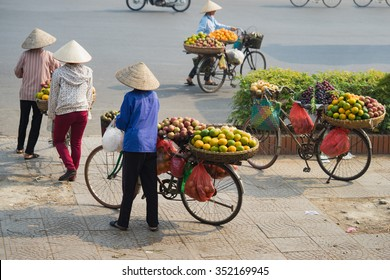 Vietnamese vendors with tropical fruit loaded basket on bike