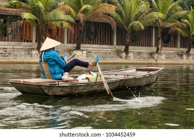 Vietnamese woman in conical hat, bright blue jacket and sandals rowing her boat with her feet at Tam Coc River, with wheels decorating bank wall in the background, Ninh Binh, Vietnam