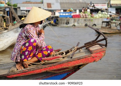 Vietnamese Woman on a Boat at a Morning Floating Market in the Mekong Delta.