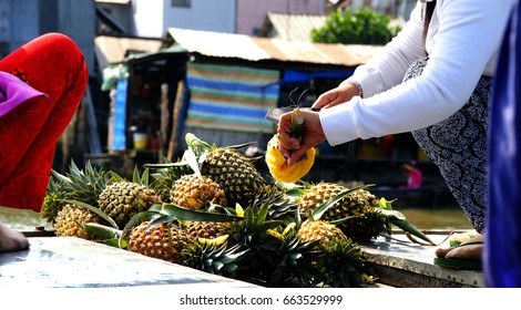 Vietnamese woman prepares pineapple for eating,  at the Cai Rang floating market on the Mekong River,  Vietnam