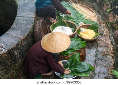 Vietnamese woman preparing to make Chung Cake, the Vietnamese lunar new year Tet food outdoor by old well and pond