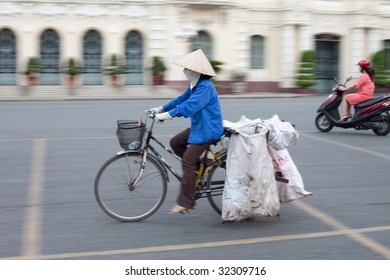 Vietnamese woman riding her bicycle with an iconic conical hat through Ho Chi Minh City. Note panning shot with motion blur.