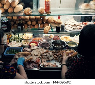 Vietnamese woman sell Vietnam bread on cart at night street food, stuffed food with meat, pork bologna, pickle, a famous and popular food that cheap, quick, Ho Chi Minh city
