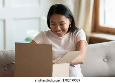 Vietnamese woman sit on sofa in living room opens received delivered parcel feels happy. Concept of trusted fast quick transport company delivery service, e-shopping sales discounts satisfied client