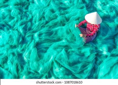 Vietnamese woman sitting repair the fish net