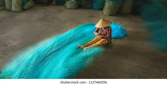 Vietnamese woman sitting repair the fishing net. Bac Lieu city, Vietnam