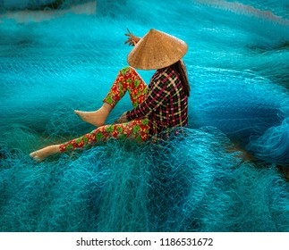 Vietnamese woman sitting repair the fishing net. Bac Lieu city, South Vietnam