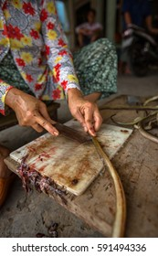 Vietnamese woman slices eels for food