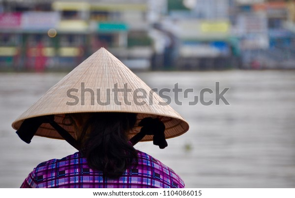 Vietnamese woman with tradional hat looking at the Mekong river