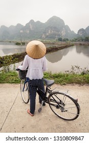 Vietnamese woman with traditional conical straw hat on bicycle. Beautiful Landscape of rice fields and mountain Scenery at Nature reserve Trang An and Tam Coc, Ninh Binh Province, Vietnam