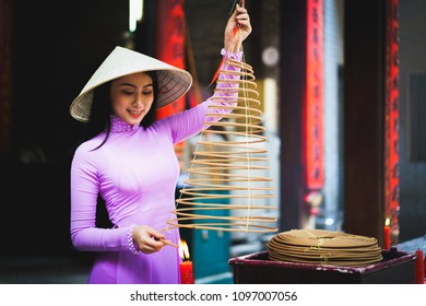 Vietnamese woman in traditional dress praying with incense stick in the burning pot of the Chinese temple, Ho Chi Minh Vietnam