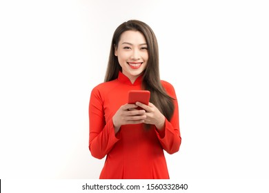 Vietnamese woman in traditional dress standing and using mobile phone isolated over white background