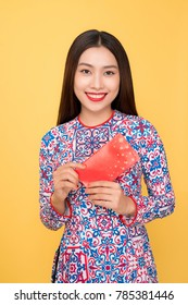 Vietnamese woman traditional festival costume Ao Dai, holding red money pockets.