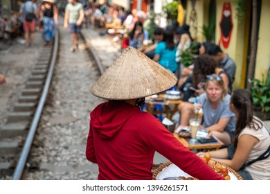 Vietnamese woman vendor walking along railroad with people drink coffee or walking on railways waiting for train to arrive on railway road in Hanoi, Vietnam.