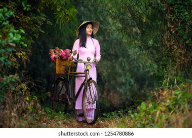 Vietnamese woman wear Ao dai Vietnam traditional dress and Vietnam hat with bicycle and lotus flower in basket at ho chi minh city of Vietnam.