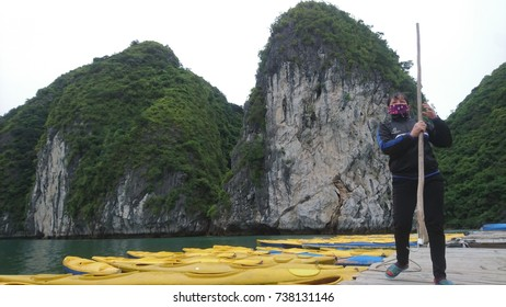 A Vietnamese woman at work while putting the kayaks in order for tourists at Ha Long Bay, Vietnam