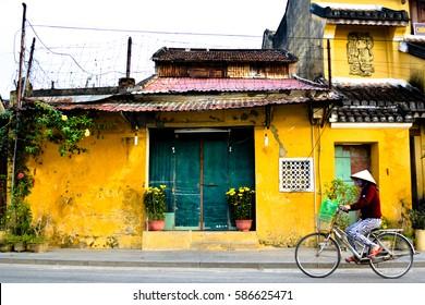 Vietnamese Women on Bike in Front of Yellow Building