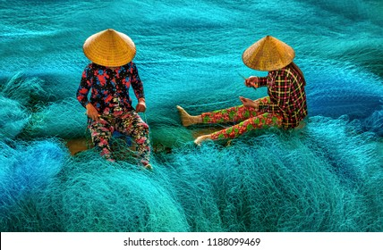 Vietnamese women are sitting repairing fishing nets in a repair shop. South Vietnam