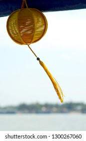 A Vietnamese woven yellow lanten hangs from a wooden beam. Its long tassle is swaying in the breeze. In the background is a bay, with a distant headland with houses.