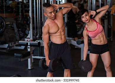 Vietnamese young couple doing dumbbell side bends together in the gym