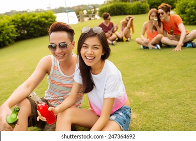 Vietnamese young couple sitting on the grass and drinking beer at the party