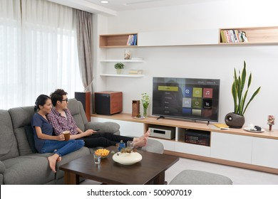 Vietnamese young couple watching smart tv at home