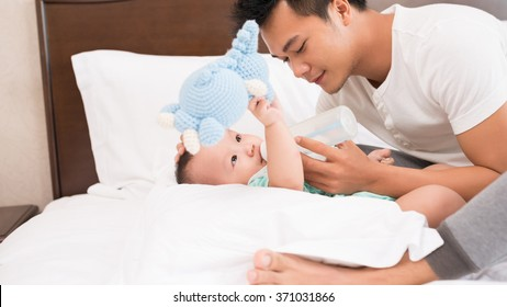 Vietnamese young father feeding his baby with milk