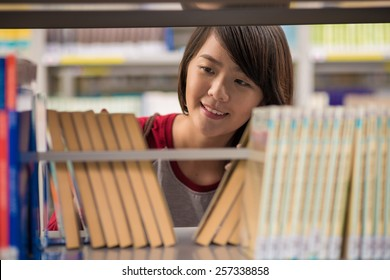 Vietnamese young girl searching for book in a library