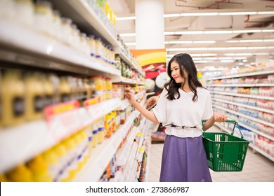 Vietnamese young lady choosing products at supermarket