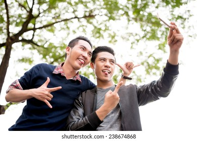 Vietnamese young men pulling out tongues while talking selfie