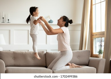 Vietnamese young mother holding hands of little asian toddler lively daughter while she jumping on couch in living room. Active time with children, fun and fit, playtime with child at home concept