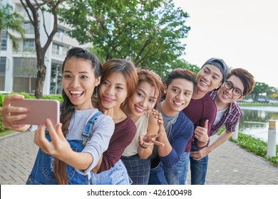 Vietnamese young people standing in a row to make funny selfie