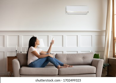 Vietnamese young woman relaxing on comfy couch in contemporary living room with air conditioner, holding remote control turning on or off cooler system, setting comfortable temperature at modern home
