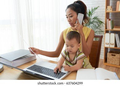Vietnamese young woman working from home when her baby is playing on laptop