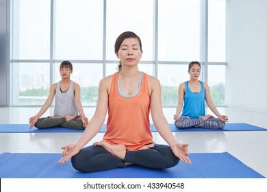 Vietnamese young women meditating in yoga class