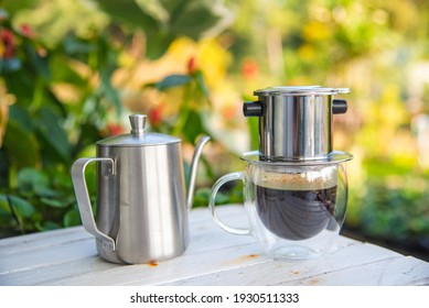 Vietnamese-style drip coffee and kettle on white table